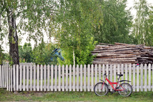 Red Bicycle On The Background Of A Wooden Fence Under The Birch