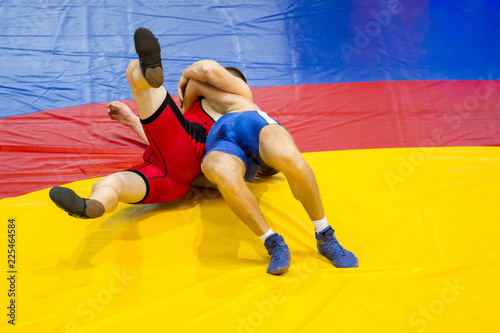 Photo  Two young men in blue and red wrestling on a yellow wrestling carpet in the gym