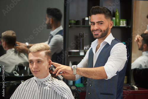 Handsome barber trimming client's haircut, looking at camera and smiling.