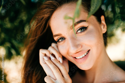 Fotografía  Closeup emotional  lifestyle portrait of adorable cute beautiful young cheerful coquette girl with big natural lips and blue happy eyes outdoor at nature