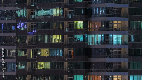 Fototapeta Windows of the multi-storey building of glass and steel lighting inside and moving people within timelapse obraz na płótnie