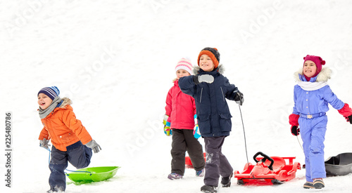 Obraz childhood, sledging and season concept - group of happy little kids with sleds in winter - fototapety do salonu