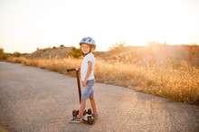 Little Sport Healthy Kid In Helmet Stands On Empty Road With Scooter In Sunset