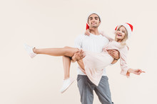 Happy Man In Santa Hat Carrying Beautiful Young Woman And Smiling At Camera Isolated On Beige