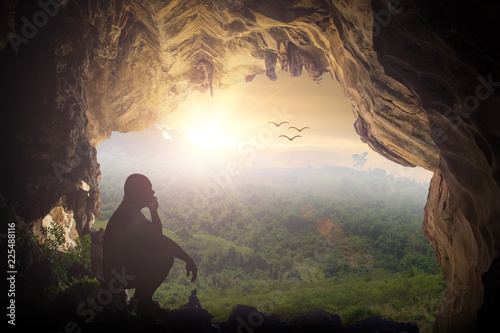 Fotomural Silhouette humble man sitting on a rock in cave looking at birds flying on autumn sunset background