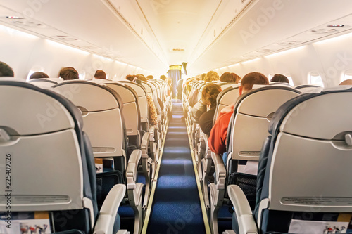 Commercial aircraft cabin with rows of seats down the aisle
