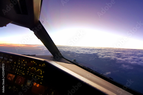 In airplane cockpit view, airplane flying over the cloud during sunset in the evening Tablou Canvas