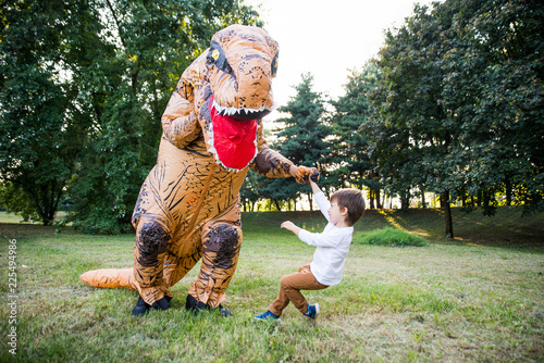 Vászonkép Father and son playing at the park, with a dinosaur costume, having fun with the