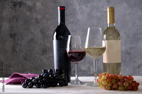 Two bottles of red and white wine with matte black & white blank labels on concrete wall background. Wineglasses half full with vintage expensive shardonnay & pinot noir, grapes. Close up, copy space.