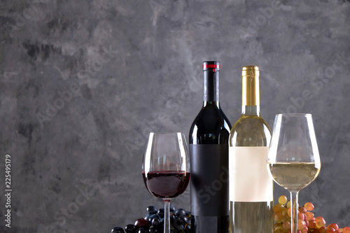Foto op Aluminium Bar Two bottles of red and white wine with matte black & white blank labels on concrete wall background. Wineglasses half full with vintage expensive shardonnay & pinot noir, grapes. Close up, copy space.