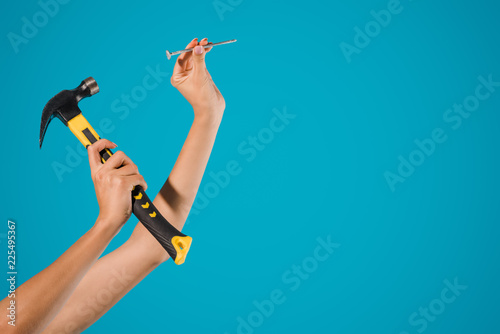 Fotografia  cropped shot of woman holding hammer and nail in hands isolated on blue