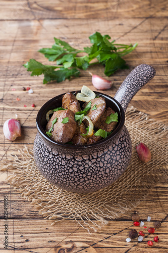 Baked chicken liver with onion in a ceramic cocotte on a wooden rustic table.