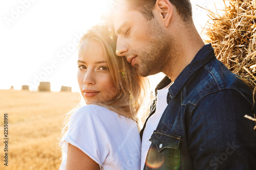 Obraz na plátně Photo of gorgeous couple man and woman walking on golden field after harvesting,