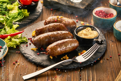 Foto op Canvas Vlees Grilled sausages with sauce on a wooden table