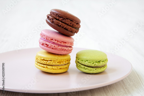 In de dag Bakkerij Colorful macarons on pink plate on a white wooden background, side view. Close-up.