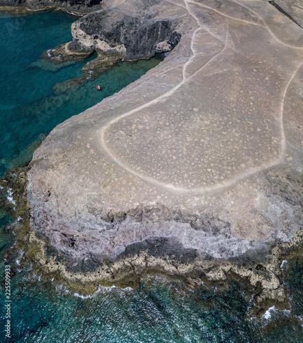 Vista aerea delle coste frastagliate e delle spiagge di Lanzarote, Spagna, Canarie. Gommone rosso ormeggiato in una caletta. Strade e sentieri sterrati. Percorsi a piedi per esplorare l'isola