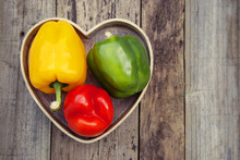 Green, Yellow And Red Bell Pepper Over Rustic Textured Wooden Background. Healthy Vegetables, Food.