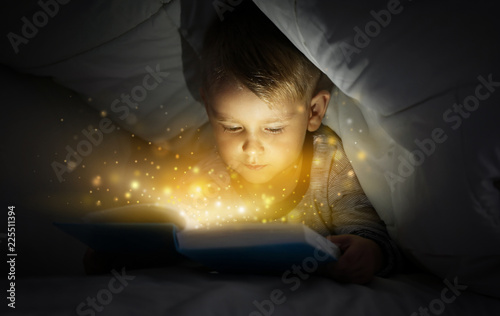 Fototapeta Cute little boy reading book in bed under blanket