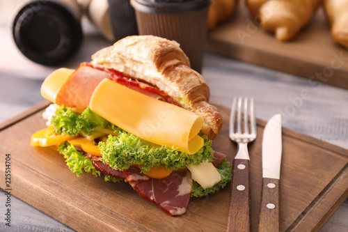 Tasty croissant sandwich with meat on wooden board