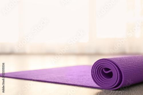 Photo Purple yoga mat on floor indoors