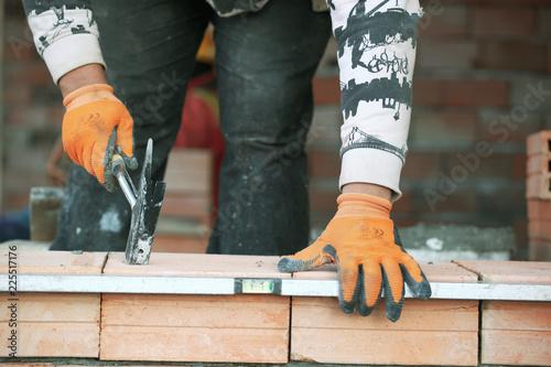 Fototapeta Industrial bricklayer installing bricks on construction site. obraz na płótnie