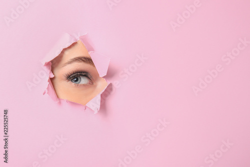 Fotomural  Eye of beautiful young woman visible through hole in pink teared paper