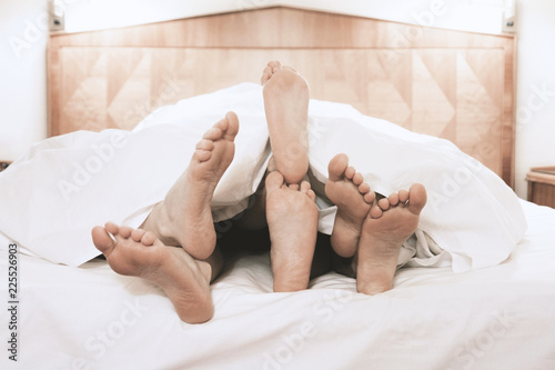 Photo  three pairs of feet lying together under bed cover in bedroom, threesome group s