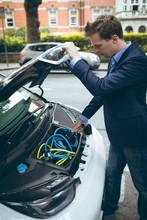 Businessman Charging Electric Car At Charging Station