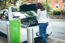 Businesswoman Charging Electric Car At Charging Station