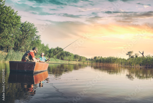 Dad and son fishing from a boat