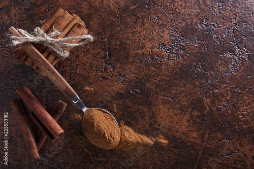 Fotobehang Kruiderij Cinnamon sticks and powder in spoon on a old copper table .