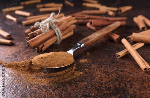 Fotobehang Kruiderij Cinnamon sticks and powder in spoon .