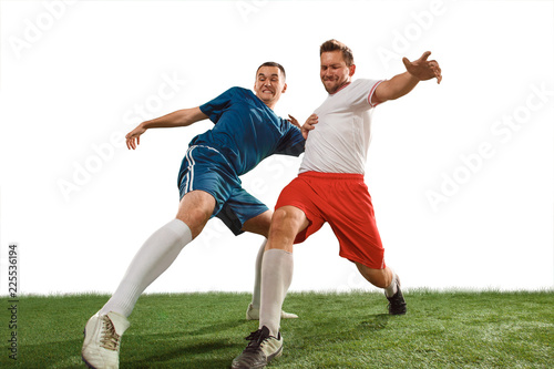 Fotobehang voetbal Football players tackling for the ball over white background. Professional football soccer players in motion isolated white studio background. Fit jumping men in action, jump, movement at game.
