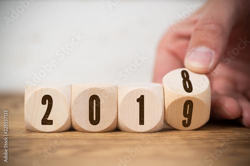 фотографія  Hand dreht Würfel und symbolisiert Jahreswechsel zwischen 2018 und 2019