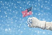 Female Hand In A Knitted Mitten With A Snowflake With An American Flag On The Winter Snowfall Background. The Concept Of Winter In America