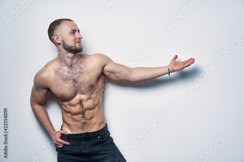 Fotografie, Obraz  Smiling muscular shirtless man directing an arm at blank copy space for advertis