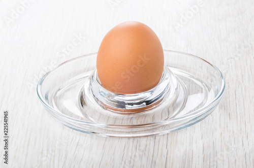 Fotografía  Boiled brown chicken egg on glass stand on table
