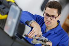 Technician Holding Pliers In Workshop
