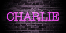 First Name Charlie In Pink Neon On Brick Wall