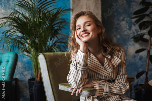 Fotografia  Young cheerful woman with wavy hair in striped trench coat leaning on hand happi