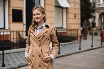 Young smiling woman in trench coat joyfully looking in camera while walking around cozy city street