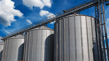 Steel Grain Silos Against Blue Sky With White Clouds