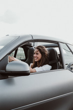 Smiling Young Woman Driving Car