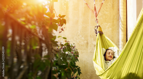 Fotografie, Obraz  happy young woman relaxed lies in a hammock on the balcony House