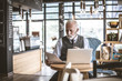 Senior businessman working at bar restaurant.