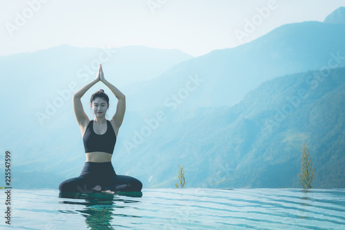Fotobehang School de yoga Beautiful Attractive Asian woman practice yoga Lotus pose on the pool above the Mountain peak in the morning in front of beautiful nature views in SAPA vietnam,Feel so comfortable and relax in holiday