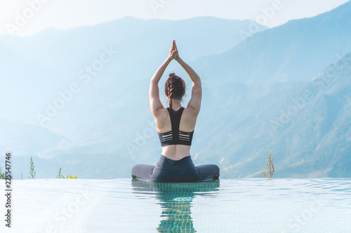 Fotobehang Ontspanning Beautiful Attractive Asian woman practice yoga Lotus pose on the pool above the Mountain peak in the morning in front of beautiful nature views in SAPA vietnam,Feel so comfortable and relax in holiday