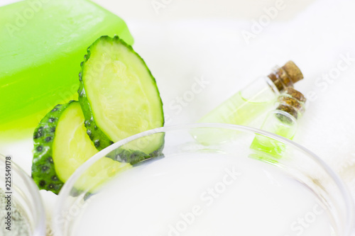 Canvas Prints Fresh vegetables Cucumber home spa and hair care concept. Sliced cucumber, bottles of oil, sea salt, bathroom towel. White board background