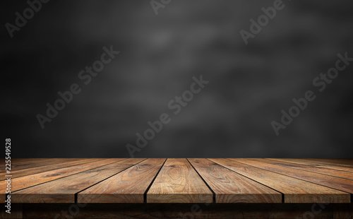 Wooden table with dark blurred background. - 225549528