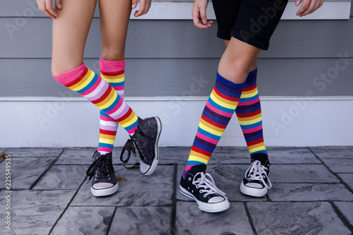 Fotografie, Obraz  Tween Girls Legs with  Colorful Striped Socks and Tennis Shoes